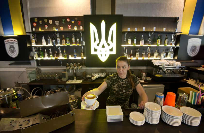 A picture taken on May 22, 2015 shows a bartender serving coffee in the Karatel bar in Kiev. — AFP pic