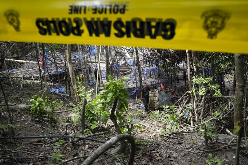 Policemen make their way through abandoned human trafficking camp in the jungle close the Thailand border at Bukit Wang Burma in northern Malaysia May 26, 2015.— Reuters pic
