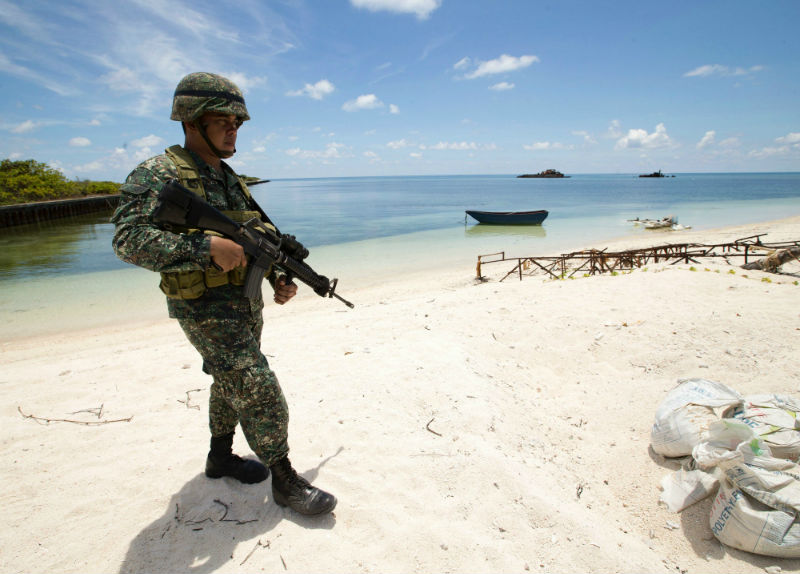 Philippine soldier Tychico Octobre patrols a beach in Pagasa Island (Thitu Island) at the Spratly group of islands in the South China Sea, west of Palawan, on May 11, 2015. — AFP pic