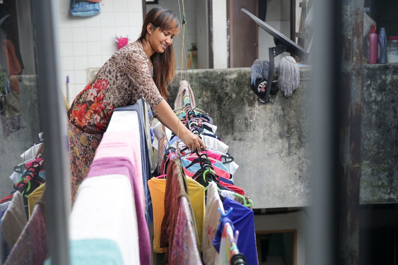 Sui doing laundry at the top floor of the old shophouse, right outside their room.