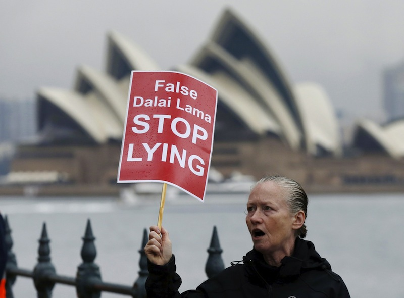 A woman, aligned with a protest by Shugden Buddhists, shouts slogans outside the venue where the Dalai Lama spoke to a convention on wellness at Sydney's Luna Park, June 10, 2015. — Reuters pic