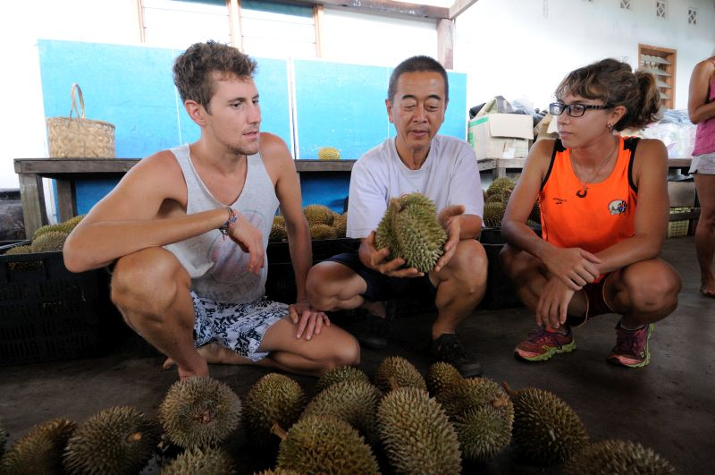 Lindsay Gasik and Ryan Lewis have a chat with farm owner Chang Teik Seng about durians at his farm.