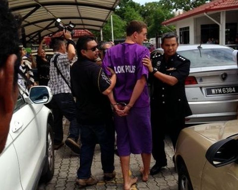 One of the four tourists being led away by the police at the Kota Kinabalu court today. ― Picture by Julia Chan