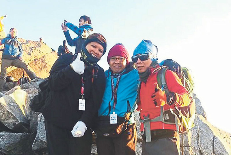 Sapinggi poses with two climbers on Mount Kinabalu in early April. He died moments after a rescue team found him on Friday. — Mail Mail pic