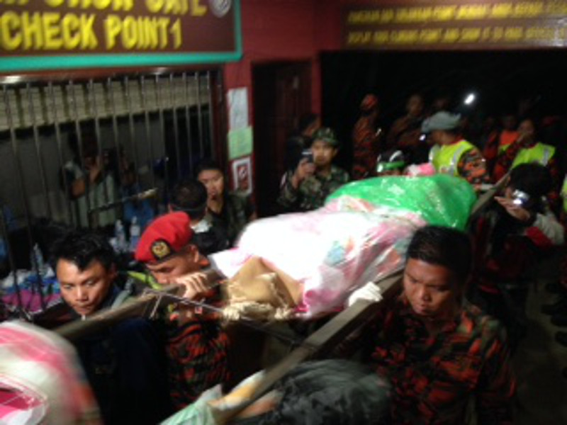 File picture shows rescue teams returning with the bodies, believed to be of a local guide and Singaporean female student recovered from Mount Kinabalu, Sabah after a 6.0 magnitude quake on June 5, 2015. — Picture by Julia Chan