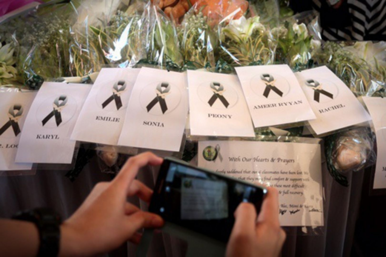 File photo of tributes bearing the names of the students and teacher confirmed dead in the Mount Kinabalu quake. — TODAY pic