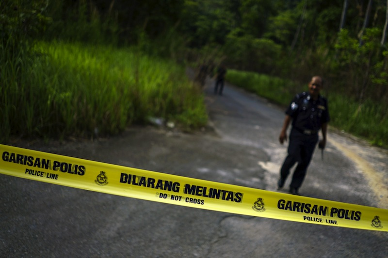 A Malaysian policeman leaves the site of the place where human remains were found, near an abandoned human trafficking camp, in the jungle close to the Thailand border at Bukit Wang Burma in northern Malaysia, May 29, 2015.— Reuters pic