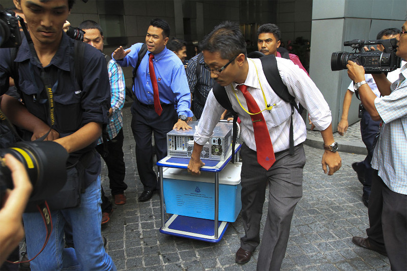 Officers from the special task force remove what looked like a CPU and a box from the 1MDB office at Menara IMC in Kuala Lumpur, July 8, 2015. Police tonight seized a laptop and documents of a deputy public prosecutor involved in a 1MDB-linked corruption probe. — Picture by Yusof Mat Isa