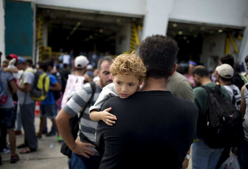 A Syrian refugee man carries a child upon their arrival onboard the Eleftherios Venizelos passenger ship at the port of Piraeus near Athens, Greece, August 24, 2015. — Reuters pic