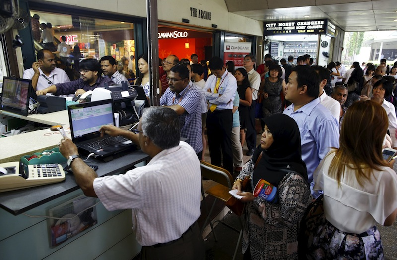 People, many looking to buy Malaysian ringgit, queue up outside moneychangers at the central business district in Singapore August 25, 2015. — Reuters pic