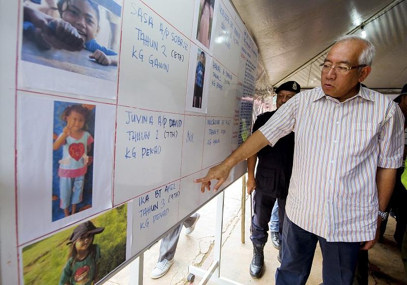 Education minister Datuk Seri Mahdzir Khalid looks at the pictures of the seven students of Sekolah Kebangsaan Tolok who went missing in Gua Musang. — File pic
