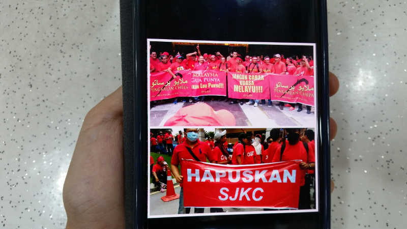 A WhatsApp posting on a mobile phone shows photographs of alleged 'seditious' banners used during the red shirts' rally. — Picture by Ida Lim