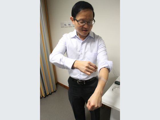 Professor Lim showing how one of their liquid-based tactile sensors can be worn.