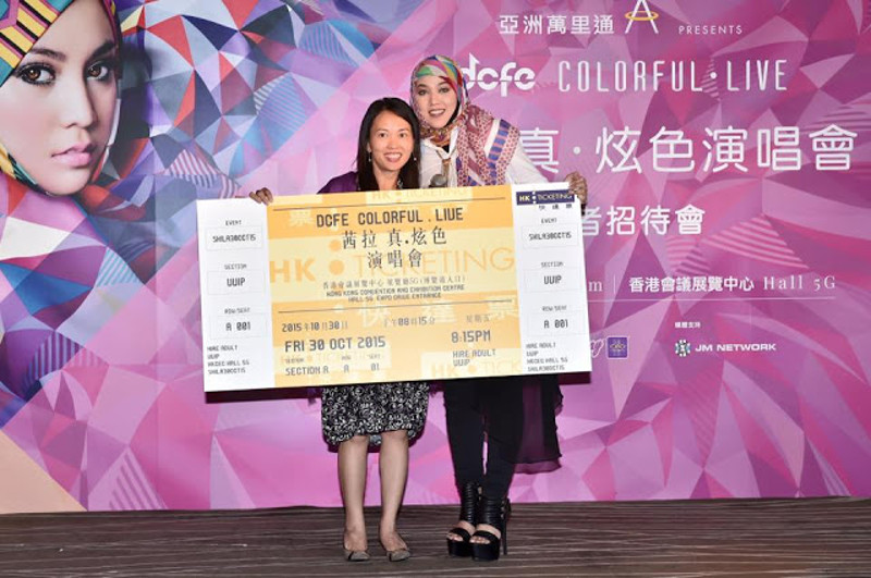 Shila Amzah and a representative from DCFE poses with a ticket to her Hong Kong concert in this photo taken from her official Facebook page.