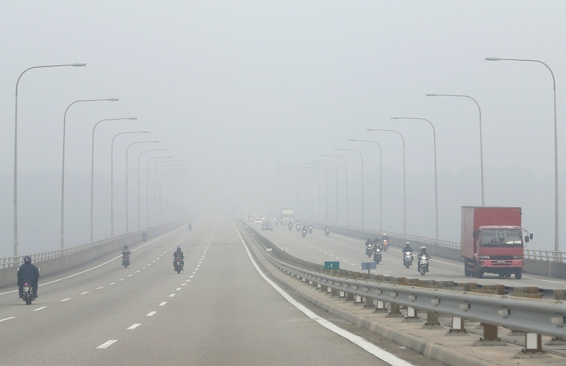 Motorists pass on a highway shrouded by haze in Malaysia. — Reuters pic