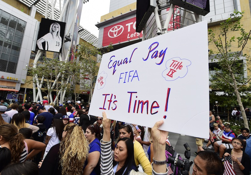 A fan holds up a sign calling for equal pay for female athletes, at the US Women's World Cup football team's championship celebration rally, at LA LIVE in downtown Los Angeles, California, July 7, 2015. — AFP pic