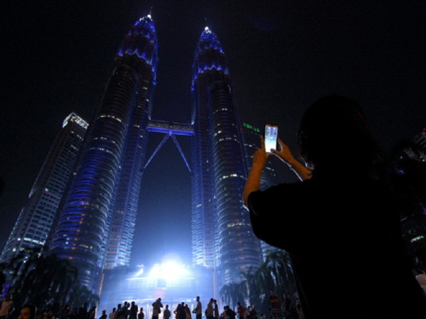 A tourist uses a smart phone to take pictures of the Petronas Twin Towers. — Bernama pic