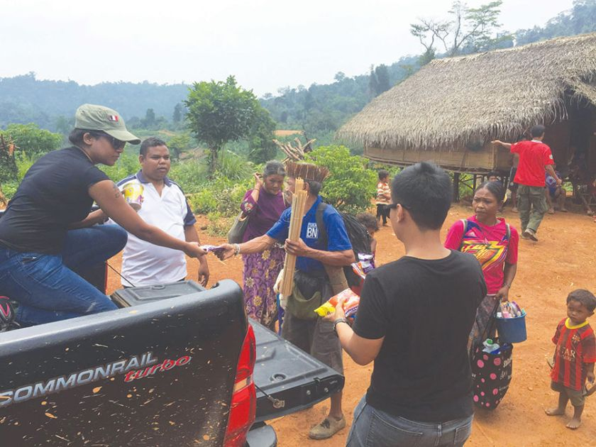 Malay Mail reporters Thasha and Emmanuel (back to camera) hand out food to villagers at Kampung Gawen. — Picture by Azinuddin Ghazali