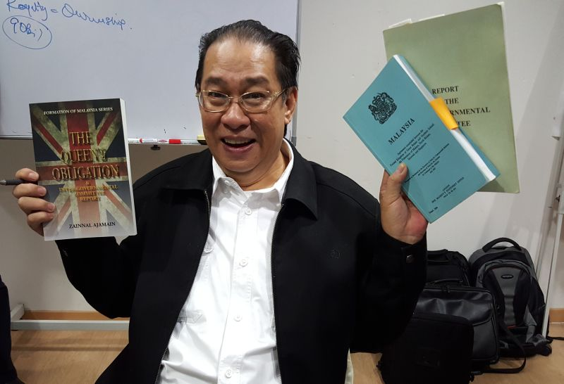 Zainnal Ajamain holding his book and the Malaysia Agreement and Inter-Governmental Committee Report at the launch of the book on Oct 28, 2015 — Picture by Sulok Tawie