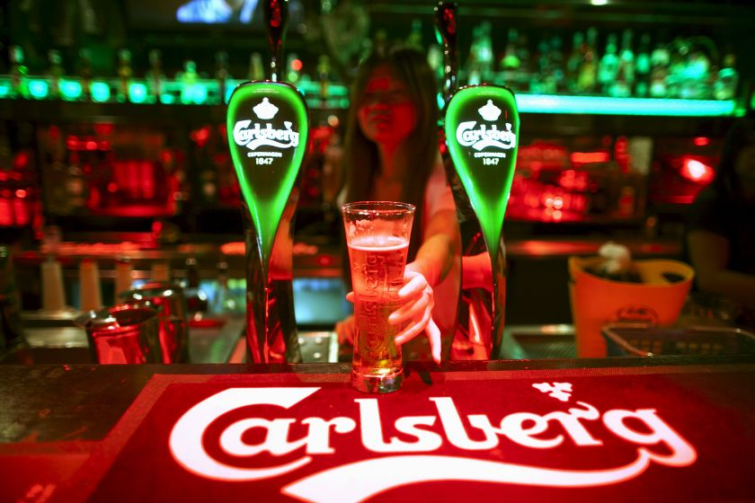 A bartender serves a glass of Carlsberg beer at a bar in Kuala Lumpur in this picture released November 9, 2015. Malaysians online have come to the defence of a female beer promoter, who was shown keeping herself calm despite being verbally assaulted by a man just for doing her job. — Reuters pic