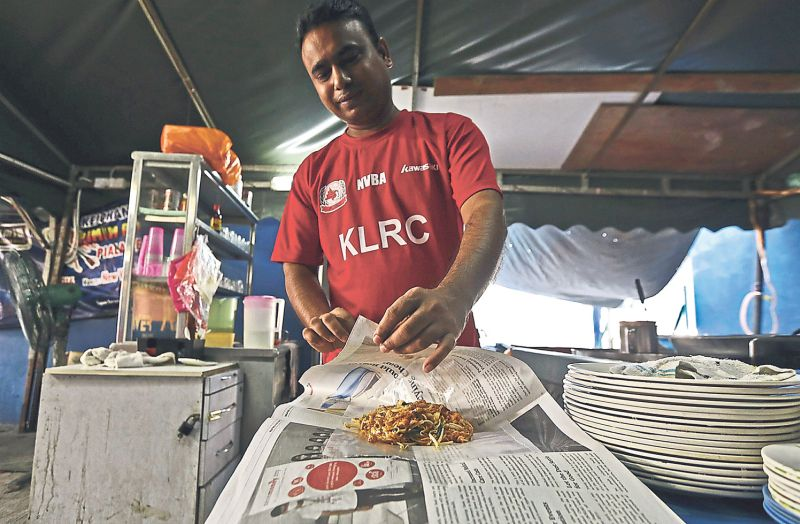 Suhaib Rahim, 32, wraps takeaway food using old newspapers at his stall in Petaling Jaya. — Picture by Azneal Ishak