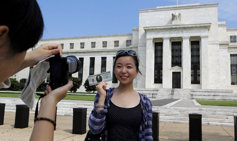 Chinese student Leyna Liu from Shanghai poses with a fake million-dollar bill in front of the Federal Reserve building in Washington, in this August 22, 2012 file photo. — Reuters pic