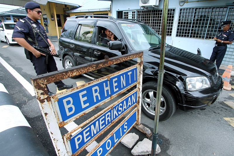 Police personnel check the identification of a driver at the Malaysia-Thailand border at the Padang Besar checkpoint in Kedah January 18, 2016. — Bernama pic