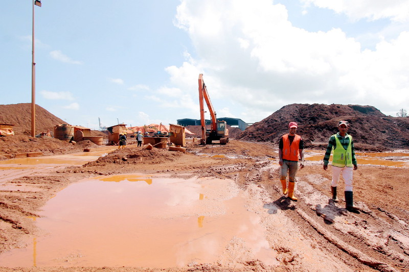 File photo of two employees walking in the bauxite reserve area at Kuantan Port without wearing protective mask, Jan 6, 2016. An air quality research fellow at UniSZA Institute of Environmental Research, Dr Azman Azid, said exposure to bauxite dust over a long period