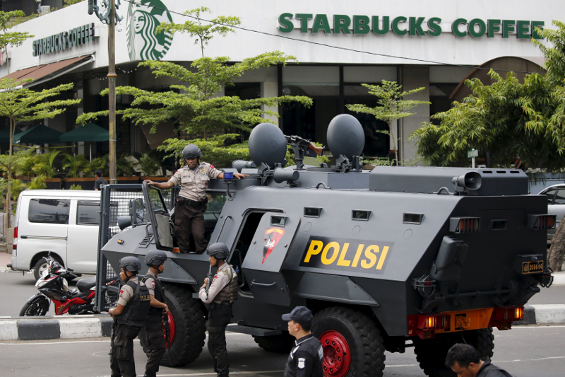 Indonesian policemen with weapons and an armoured vehicle guard in front of a Starbuck cafe at Thamrin business district in Jakarta, January 14, 2016. — File pic