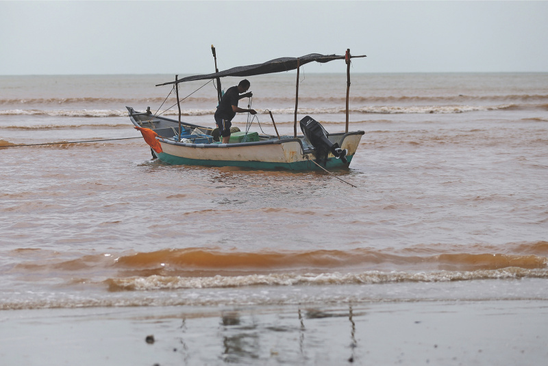 A fisherman along Pantai Balok, Kuantan. An expert has said marine life in the area will eventually die due to bauxite contamination. — Malay Mail pic