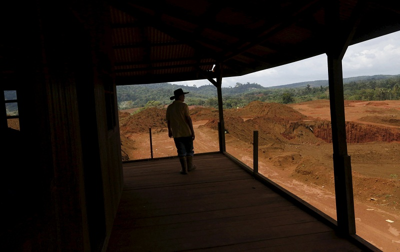A man stands on the verandah of an abandoned house once in a durian orchard, now mined by bauxite mining companies in Kuantan February 16, 2016. — Reuters pic