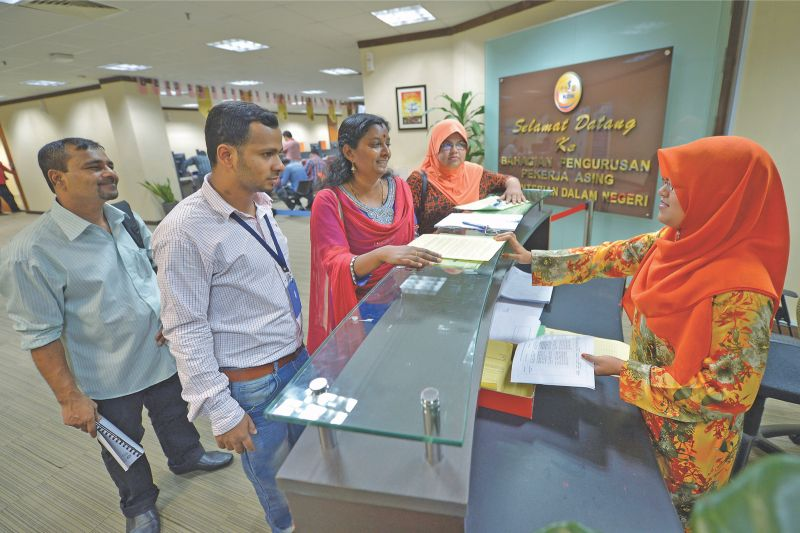 An employer renews work permits of her foreign workers. The presence of migrant workers has made it more difficult for locals to obtain jobs. ― Malay Mail pic