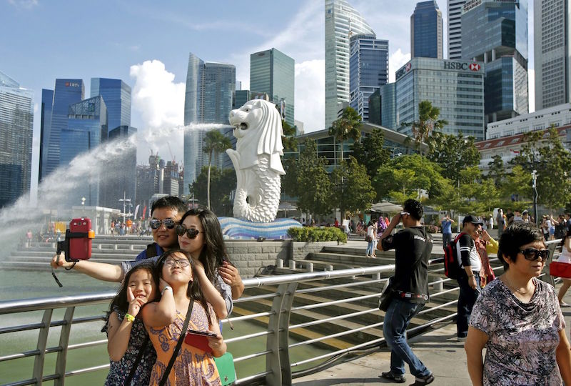 Tourists take photos by the Merlion in Singapore. — Reuters pic