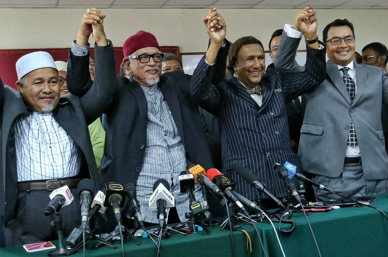 PAS president Datuk Seri Hadi Awang (second from left) and Parti Ikatan Bangsa Malaysia president Tan Sri Abdul Kadir Sheikh Fadzir (third from left) during a press conference to announce the new alliance between the two parties, in Kuala Lumpur March 16, 2016. — Picture by Saw Siow Feng