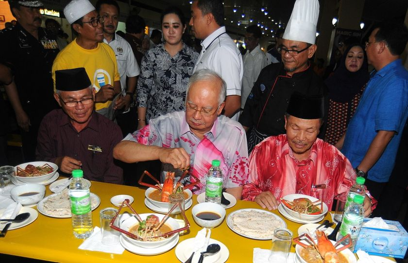 File photo shows Prime Datuk Seri Najib Razak (centre) tucking into a bowl of Sarawak laksa on March 12, 2016.With the influx of visitors in recent weeks, business is booming, especially for the laksa sellers in many parts of the city. — Bernama pic