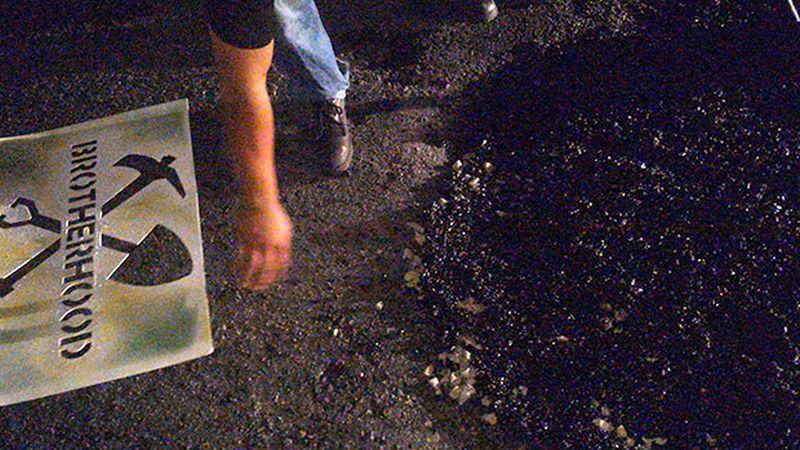 Once they are done fixing a pothole, members of the Brotherhood spray their logo on it.