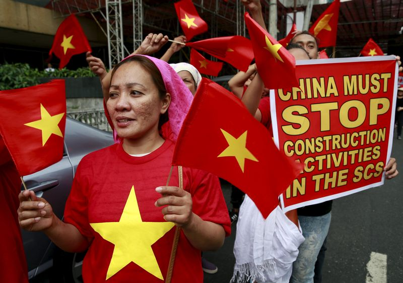 Protesters wave Vietnamese flags and hold a placard as they denounce China's military buildup in the South China Sea in front of the Chinese Consulate in Manila February 25, 2016. — Reuters pic