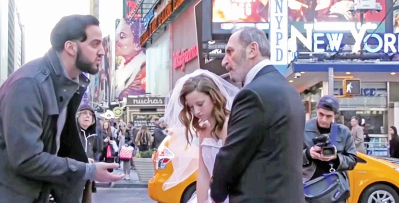 A screen grab from a YouTube video of a social experiment by Coby Persin, which saw crowds reacting to a '65-year-old man and his 12-year-old girl bride' during their 'wedding photo shoot' in the middle of New York City.