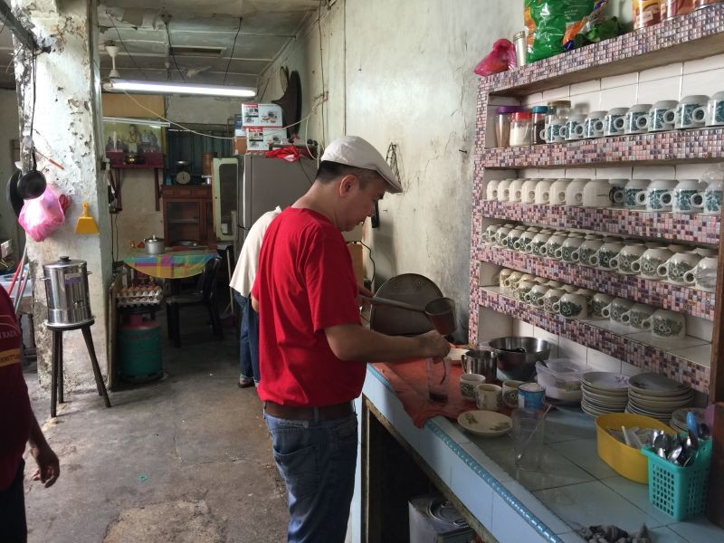 Tan Jeng Seow preparing coffee at the coffee shop his grandfather started at Hutton Lane.