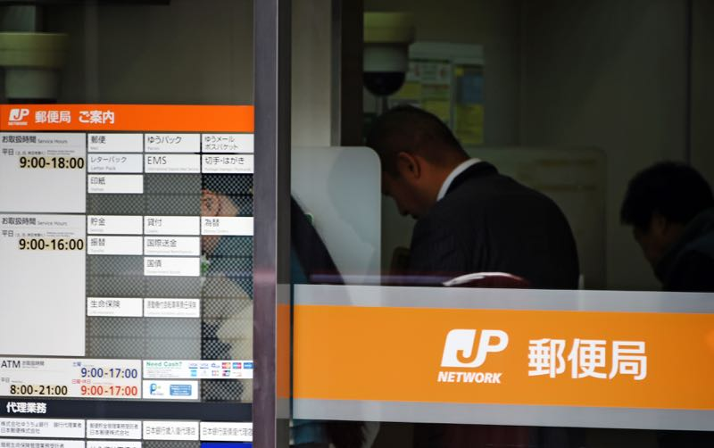Customers use an ATM at a branch of Japan Post in the Ginza shopping district of central Tokyo on December 26, 2014. ― AFP pic