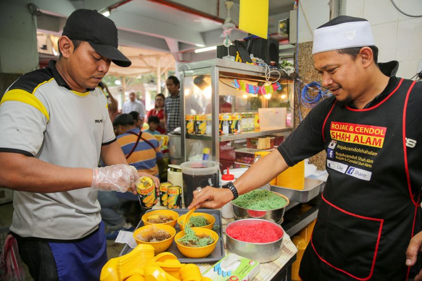 Mohd Hafez Hamed spoons the cendol into the bowls with shaved ice and syrup.
