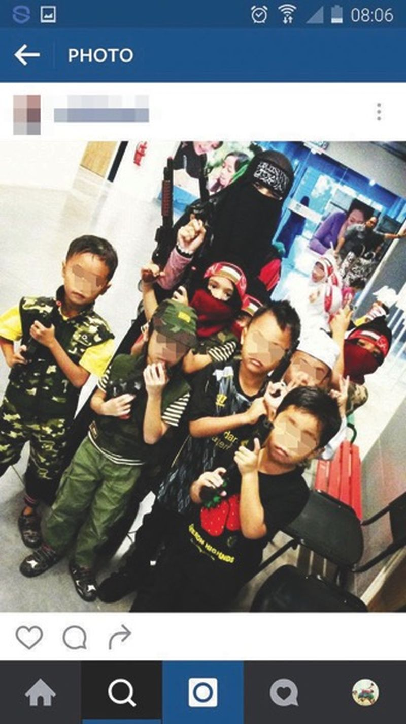 The picture on Instagram shows children possibly no older than four dressed in military camouflage outfits and carrying toy guns.