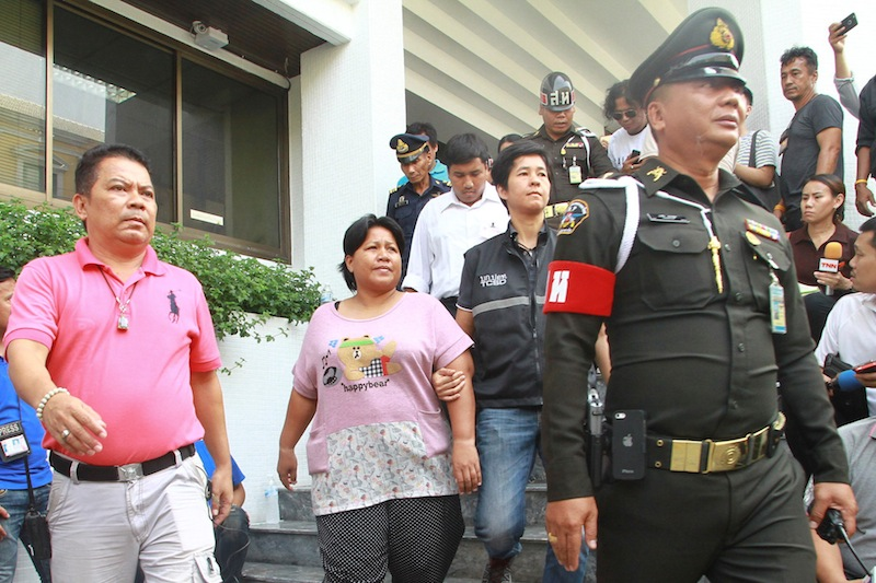 Patnaree Chankij, the mother of an anti-junta activist, is escorted by police as she leaves a military court in Bangkok, Thailand, May 8, 2016. — Reuters pic