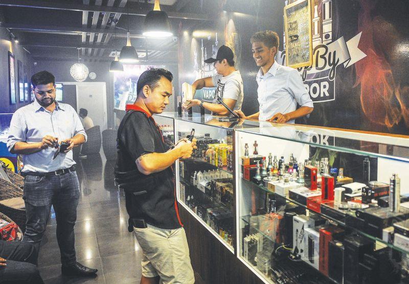 Ibnu Ridha, 28, (wearing cap) and Hazique Riefdi, 20, behind the counter at 'Drop by Vapor' in Damansara Utama Uptown.— Picture by Firdaus Latif