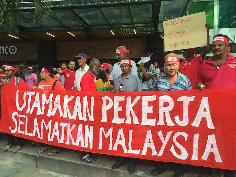 Rally participants hold a banner outside Maju Junction Mall in Kuala Lumpur May 1, 2016. — Picture by Kamles Kumar