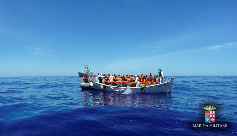 Migrants sit in their boat during a rescue operation by Italian navy ship Grecale (unseen) off the coast of Sicily, Italy. — Reuters pic