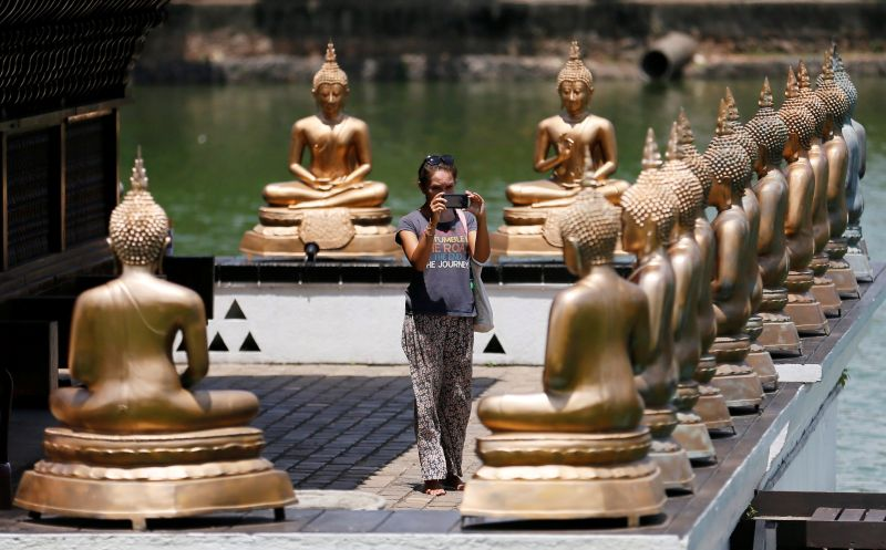 A tourist takes pictures of Buddha statues at a temple in Colombo, Sri Lanka in this file picture taken on May 7, 2016. ― Reuters pic