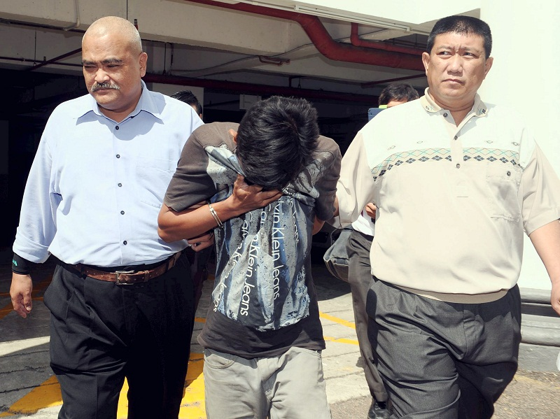 Labourer Muhammad Amirul Azwan Mohd Shakri (centre), 19, was sentenced to a total of 14 years' jail for posting insulting comments against the Tunku Mahkota of Johor, Tunku Ismail Sultan Ibrahim. — Bernama pic