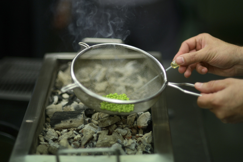 A strainer holds a few tear peas as they are smoked over coals for only seconds at Nerua, a restaurant at the Guggenheim museum in Bilbao, Spain, May 24, 2016. — Picture by Samuel Aranda/The New York Times