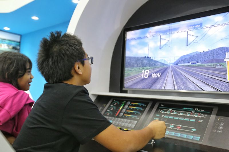 A child plays the role of a train captain in KL-Singapore HSR project exhibition at NU Sentral, Kuala Lumpur, June 15, 2016. ― Picture by Saw Siow Feng
